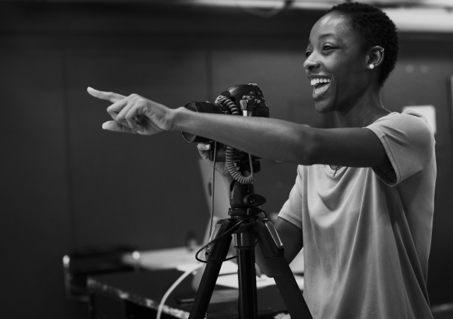 A young woman standing behind a camera, with a big smile, pointing to something out of frame.