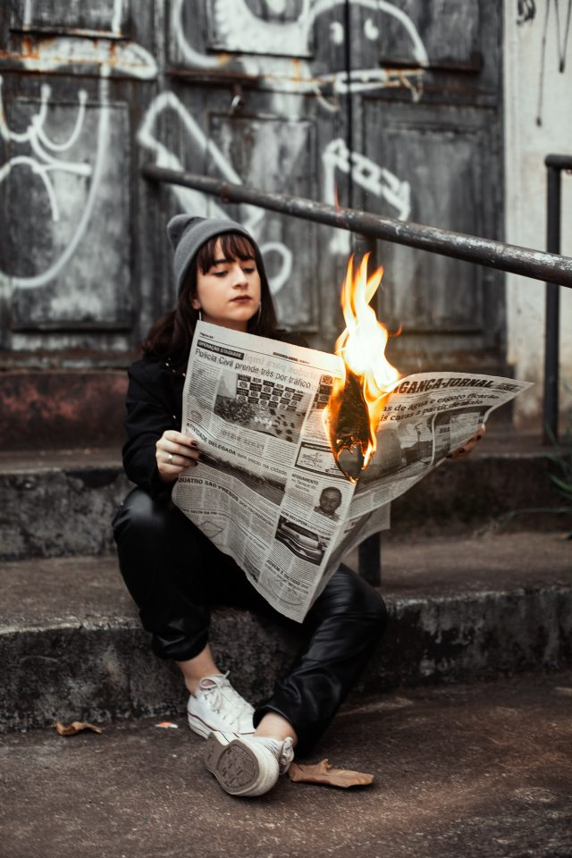 A young woman sitting on concrete steps calmly reading a newspaper that is on fire. The wall behind her is grafitied