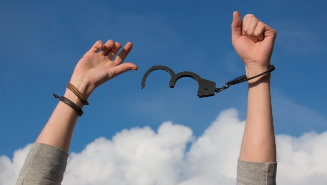 Hands breaking free of handcuffs against a blue sky