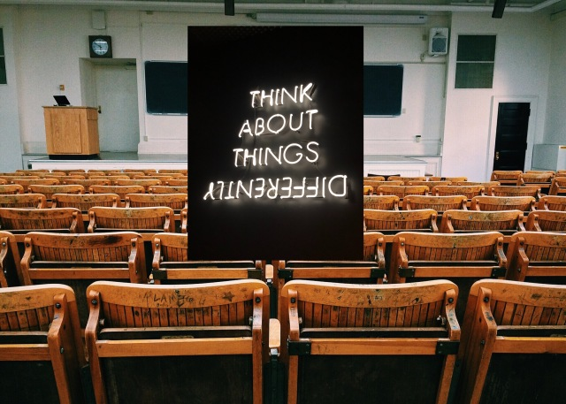 A photo of a traditional lecture theatre with wooden chairs, with another image superimposed on top. This says 'think about things differently' in neon tubes